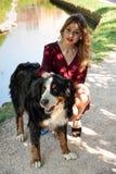 Portrait d'une belle fille s'accroupissant avec son chien par un courant images libres de droits