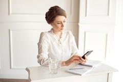 Portrait d'une belle jeune femme d'affaires de sourire de brune dans une chemise blanche se reposant sur un poste de travail mode image libre de droits