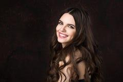 Portrait d'une belle jeune femme avec de longs cheveux sains et beau sourire sur un fond foncé photo libre de droits