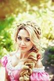 Portrait d'une belle jeune femme avec de longs cheveux tressés dans la tresse sur la nature de fond Image stock