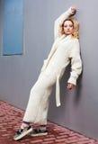 Portrait d'une belle jeune femme blonde dans une grande mode tricotée et des espadrilles de manteau blanc Streetstyle Photo stock