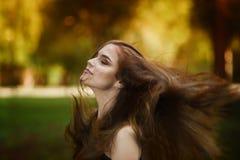 Portrait d'une belle jeune femme caucasienne avec se développer dans les longs cheveux de vent, la peau propre et le maquillage o image stock