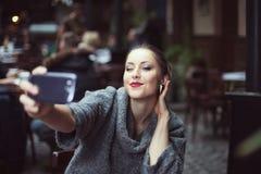 Portrait d'une belle jeune femme de sourire faisant la photo de selfie avec son smartphone Photo stock