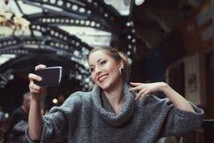 Portrait d'une belle jeune femme de sourire faisant la photo de selfie avec son smartphone Photo libre de droits