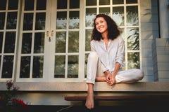 Portrait d'une belle jeune femme heureuse s'asseyant sur le porche de la terrasse avec sa maison sur le fond images libres de droits