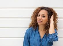 Portrait d'une belle jeune femme souriant avec la main dans les cheveux Photographie stock