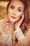 Portrait d'une belle jeune fille avec des yeux bleus, une robe douce de pêche sur un fond des feuilles d'automne Photo stock