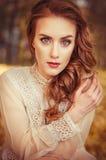 Portrait d'une belle jeune fille avec des yeux bleus, une robe douce de pêche sur un fond des feuilles d'automne Photos stock