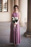 Portrait d'une belle jeune jeune mariée qui se tient entre les colonnes près du vieux bâtiment et le bouquet nuptiale de particip Photo stock