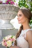 Portrait d'une belle jeune mariée, bouquet d'une jeune mariée et un diadème photographie stock libre de droits
