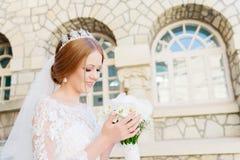 Portrait d'une belle jeune mariée dans une robe blanche et un bouquet des fleurs dans des ses mains photo libre de droits