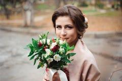 Portrait d'une belle jeune mariée dans une robe rouge avec un bouquet l'épousant dans une main photo libre de droits