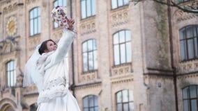 Portrait d'une belle jeune mariée, dans une robe, un voile et un manteau de fourrure blancs la jeune mariée est rotation, et sour banque de vidéos