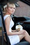 Portrait d'une belle jeune mariée dans une voiture avec un bouquet des fleurs images stock