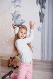 Portrait d'une belle petite fille dans a dans les bouche-oreilles dans l'inte Image stock