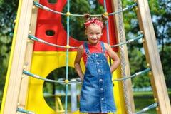 Portrait d'une belle petite fille dans le costume de denim et le T-shirt rouge photo stock