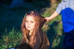 Portrait d'une belle petite fille tandis que son frère d'enfant en bas âge tire ses cheveux photos stock