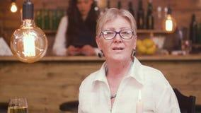 Portrait d'une belle vieille dame s'asseyant à une table dans une barre banque de vidéos