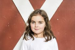 Portrait d'une belle vieille fille de cinq ans devant une porte de grange rouge Photographie stock libre de droits