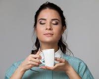 Portrait d'une brune attrayante avec une tasse Photographie stock libre de droits