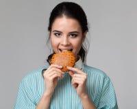 Portrait d'une brune attrayante mordant un biscuit Photo stock