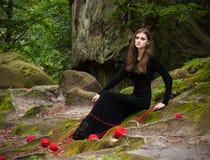 Portrait d'une brune dans une robe noire qui se repose sur la mousse verte avec des embrouillements rouges des fils Image libre de droits