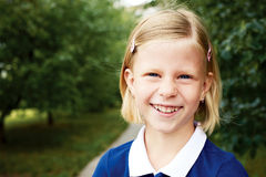 Portrait d'une écolière de sourire dans une robe bleue Photos stock