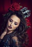 Portrait d'une couronne de port de femme de brune sur le fond rouge image stock