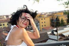 Portrait d'une dame aux cheveux courts foncée, mal peigné du vent, sur un balcon avec un fond de ville photos stock