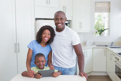 Portrait d'une famille de sourire heureuse utilisant le comprimé numérique Image stock