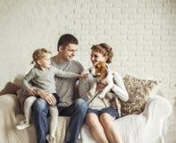 Portrait d'une famille heureuse et d'un animal familier se reposant sur un sofa Image libre de droits
