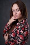 Portrait d'une femelle dans une robe color?e sur le fond gris photo stock
