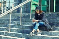 Portrait d'une femme élégante dans le chapeau et des lunettes de soleil avec le smartphone image stock