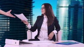 Portrait d'une femme d'affaires Brune en verres se reposant dans le bureau et les signes les documents apportés par l'employé clips vidéos