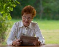 Portrait d'une femme d'affaires d'un âge lisant un journal Photo libre de droits