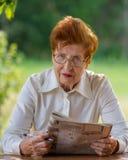 Portrait d'une femme d'affaires d'un âge lisant un journal Photos libres de droits