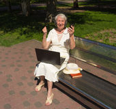 Portrait d'une femme agée, avec l'ordinateur - ordinateur portable et téléphone Images stock