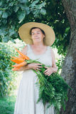 Portrait d'une femme agée dans un chapeau tenant une carotte Photographie stock libre de droits