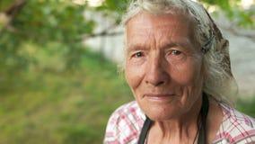 Portrait d'une femme agée dans un foulard Le vent hésite ses cheveux gris, elle regarde dans l'appareil-photo et clignote clips vidéos