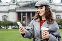 Portrait d'une femme assez de sourire à l'aide du téléphone portable tout en tenant la tasse de café sur une rue de ville photo stock