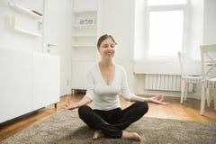 Portrait d'une femme attirante s'asseyant dans la pose de lotus photo stock
