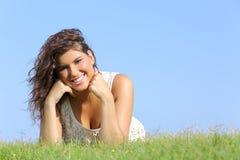 Portrait d'une femme attirante se trouvant sur l'herbe Photographie stock libre de droits