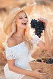 Portrait d'une femme avec du raisin dans des mains Photo stock