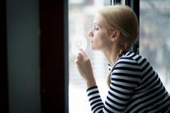 Portrait d'une femme blonde dans l'amour à la fenêtre Photographie stock libre de droits