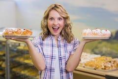 Portrait d'une femme blonde de sourire ayant une pâtisserie Photo stock
