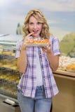 Portrait d'une femme blonde de sourire ayant une pâtisserie Images stock