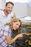 Portrait d'une femme blonde de sourire montrant une pâtisserie Photographie stock