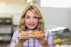 Portrait d'une femme blonde de sourire montrant une pâtisserie Images stock