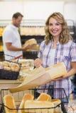 Portrait d'une femme blonde de sourire prenant un pain sur son sac de papier Images stock