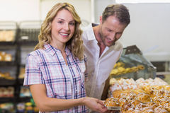 Portrait d'une femme blonde de sourire prenant une pâtisserie Image stock